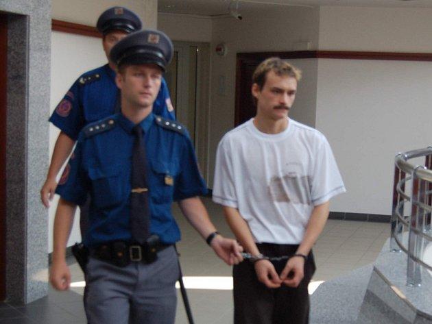 Eskorta přivádí Michala Děčka k vyhlášení rozsudku.