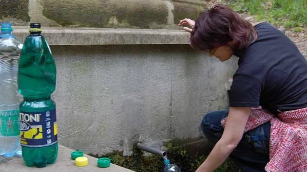 Mladá žena nabírá u studánky vodu.