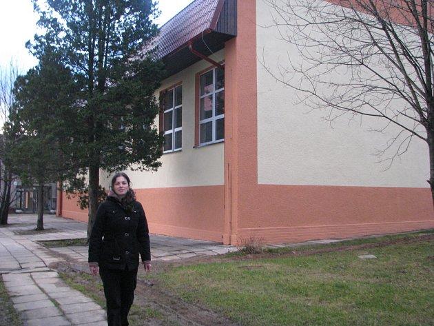Žena jde ve Vendryni kolem opravené tělocvičny.