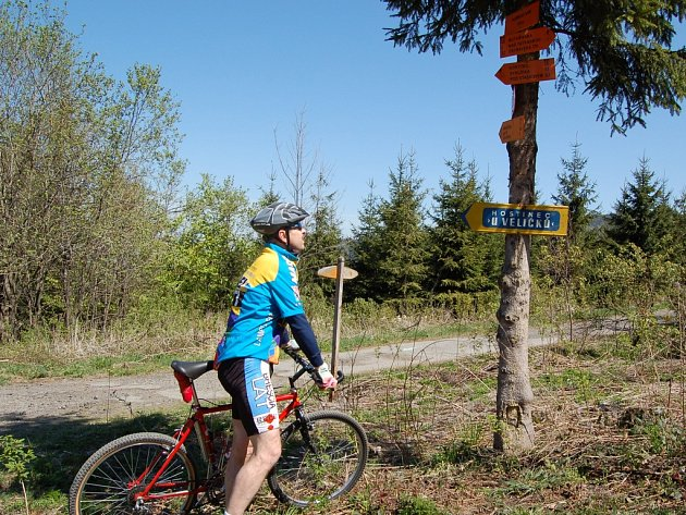 Cyklista si prohlíží rozcestník na Albínově náměstí, který označuje nejkratší cyklotrasu vedoucí na vrcholek Lysé hory.