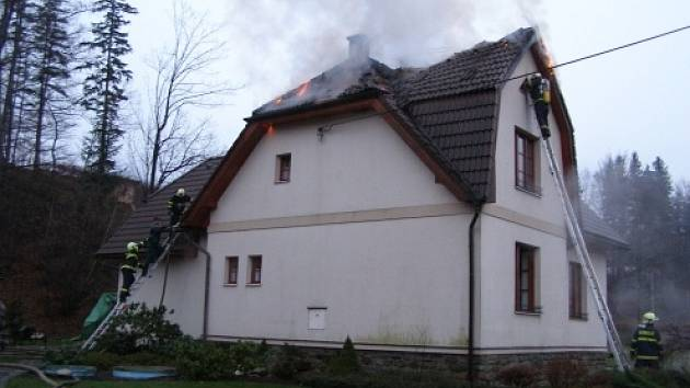 Hasiči právě šplhají po žebřících na hořící střechu domu v Čeladné. Během zásahu použili i termokameru.