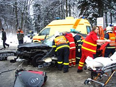 Záchranáři na snímku vyprošťují z nabouraného vozu zraněného řidiče, jenž se v Jablunkově střetl s kamionem. Podle lékařů si delší dobu poleží v nemocnici.