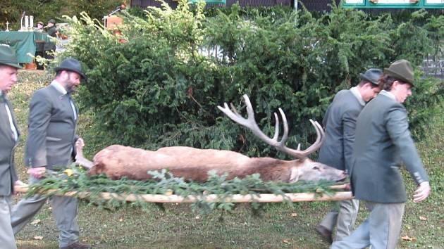 Myslivci nesou jelena, který ležel před oltářem jako trofej lovu.