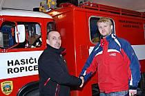 Pomáhají si. Vlevo Roman Bartoš, velitel SDH Vendryně, vpravo velitel ropické jednotky Marek Haltof. Předání staré motorové stříkačky a dalších věcí proběhlo v neděli 20. února.