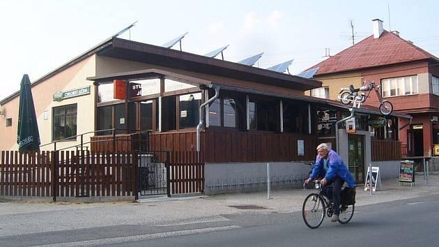 Muž projíždí kolem restaurace Cyklorest v Lučině.