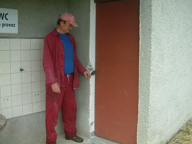 Zaměstnanec  služeb se dívá na vypáčené dveře skladu , který jim vykradl zloděj.