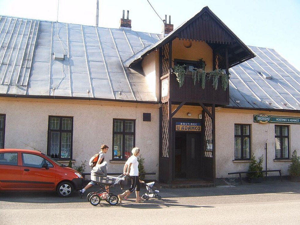 Lidé se procházejí kolem hostince U Adamců v Pržně.
