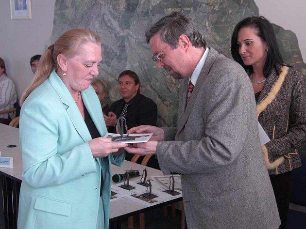 Jiří Tošner předává cenu Marii adamusové, blahopřát se chystá starostka Věra Palkovská.
