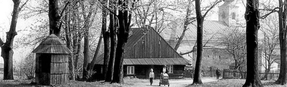 POHLED na dřevěnici stojící na místě původního fojtství v centru obce. Na pozemcích fojtství byl v roce 1768 vystavěn farní kostel sv. Hedviky, na snímku před ním stojící farské chlévy. Zcela vlevo v popředí se nachází objekt kryté studny. Rok 1983.