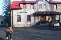 Žena projíždí na kole kolem hotelu Godula v centru Komorní Lhotky.