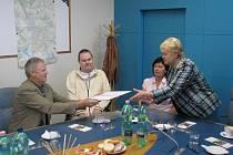 Ochrnutý hasič Tomáš Malyjurek (na snímku uprostřed) a jeho rodiče přebrali z rukou frýdecko–místecké primátorky Evy Richtrové (vpravo) dar od města.