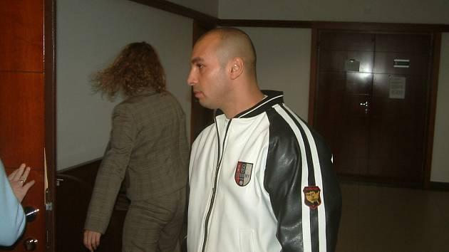 Milan Fedor vchází do soudní síně. Muž čelí obžalobě ze dvou loupeží a vydírání.