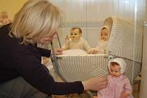 Eva Wantuloková upravuje jednu z panenek. V kočárku je vidět miminko nazývané Frantík.