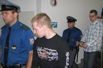 Eskorta přivádí k soudu dva muže, kteří se přiznali k vloupání do čtyřiceti objektů. V popředí Martin Jenčo, za ním jde Lukáš Kužílek.