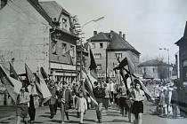 PRŮVODY byly neodmyslitelnou součástí života v socialistickém Československu. Na snímku směřuje průvod směrem z centra města po Hlavní ulici. Dům uprostřed fotky mírně v pozadí na rohu Nádražní a Hlavní ulice stojí dodnes, pár metrů od něj pak byla v roce