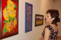 Žena si v třinecké galerii prohlíží obrazy Vladislava Raszyka.