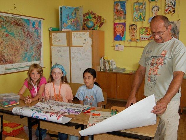 Zleva Sandra Gulkásová, Karin Malyszová a Linda Nguyenová společně se svým učitelem Zdeňkem Oborným z místecké 6. základní školy. Dívky sedí v lavici, která je podle normy, všichni žáci ve všech školách ale takové štěstí nemají.
