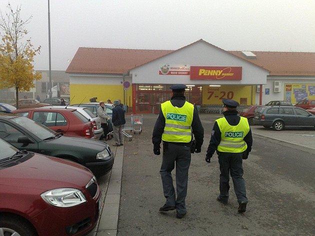 Policisté dohlížejí na zaparkované vozy u marketů ve Frýdlantě nad Ostravicí.