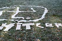Hákový kříž a nápis Hitler na trávníku