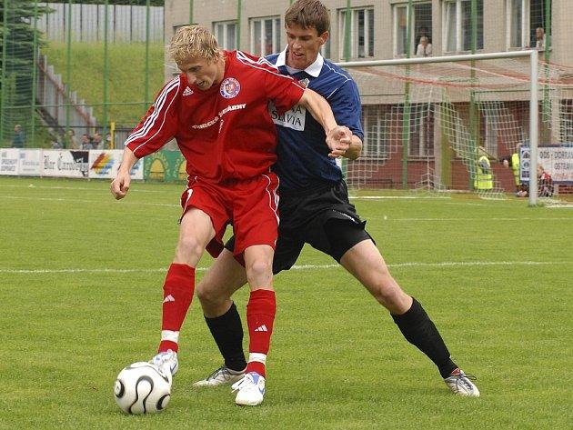 Žižkovský Milan Jambor bojuje o míč s třineckým Pavlem Malířem (v červeném).
