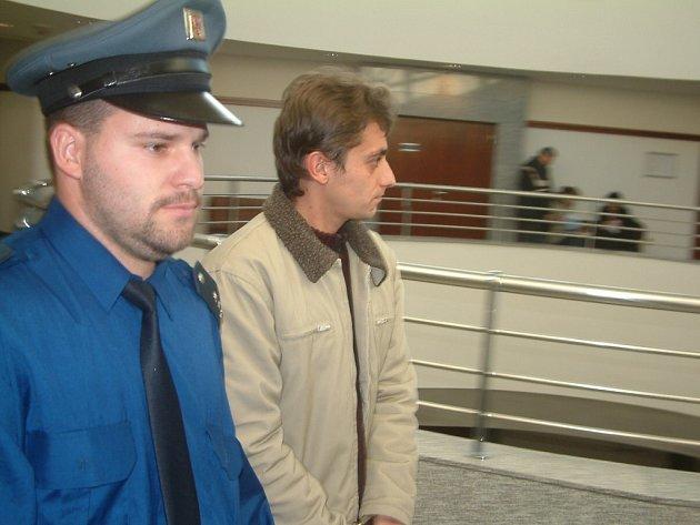 Eskorta přivádí Jiřího Táborského k soudu.