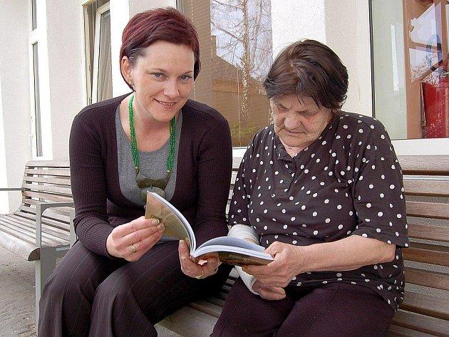 Dobrovolnice Pavlína Sobotíková (vlevo) čte Jarmile Dolenské.