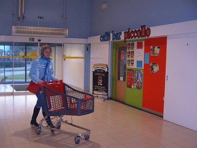 Žena s nákupním vozíkem prochází kolem Caffé bar Piccollo v Třinci.