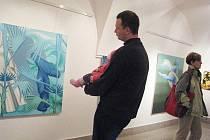 Návštěvník vernisáže si prohlíží malby Denisy Fialové v Langově domě.