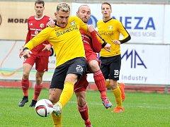 Třinecký Petr Joukl (v tmavém dresu za hráčem) atakuje sokolovského Přeučila.