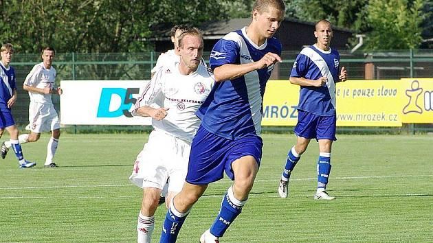 Frýdecko-místecký obránce Jan Hrdlička (v modrém) vyváží míč před třineckým Jouklem.