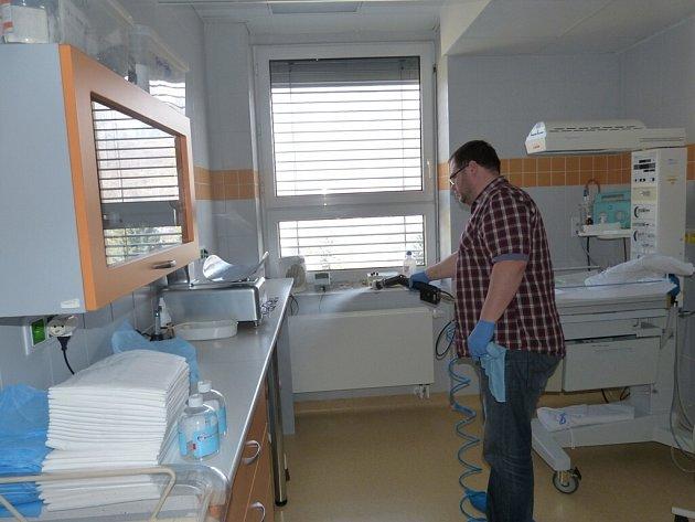 Pracovník specializované firmy provádí postřik ničící mikroorganismy v třinecké nemocnici.