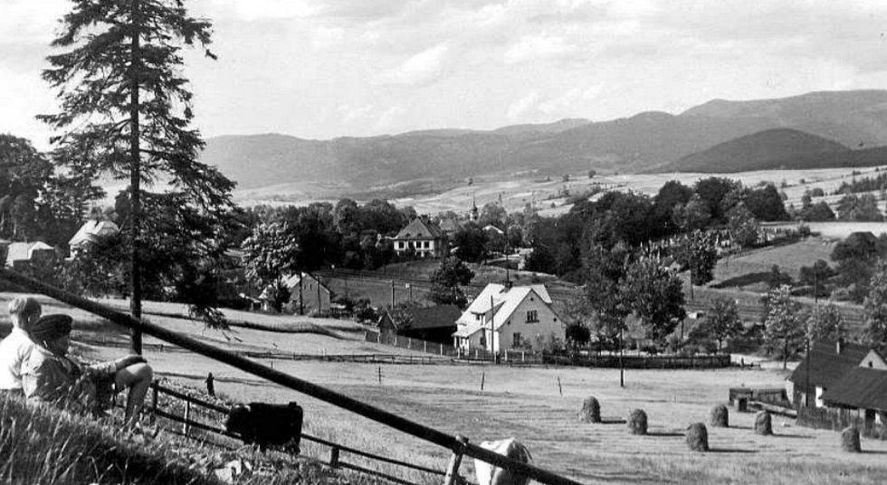 POHLED od jihozápadu na centrum obce v popředí s rodinným domem č. p. 423, za nímž je vidět budova české školy a věž farního kostela sv. Hedviky. Na protějším svahu se za železniční tratí nachází hřbitov. Rok 1947.