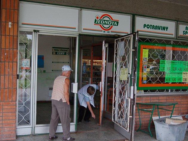 Zákazník vchází do prodejny, před kterou neznámí zlodeji odcizili bankomat plný peněz.