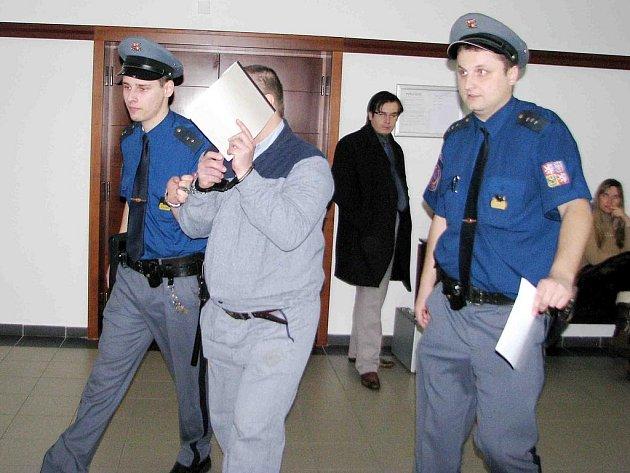 Bronislav Dimel (na archivním snímku) si během eskorty k soudu zakrývá tvář.