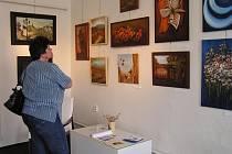 Návštěvnice si prohlíží obrazy Jany Pavelkové.
