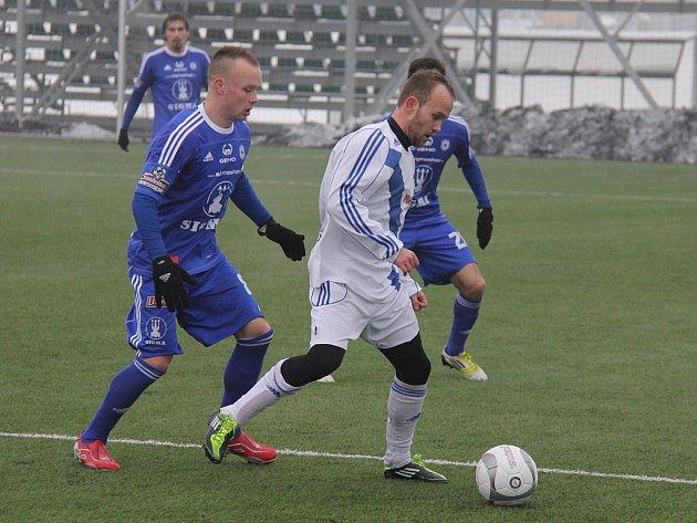 Záložník Filip Racko (v bílém) v souboji o míč s olomouckým kapitánem Janem Javůrkem.