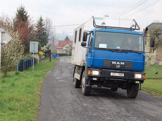 Náklaďák projíždí po úzké cestě v Lískovci mezi rodinnými domy.