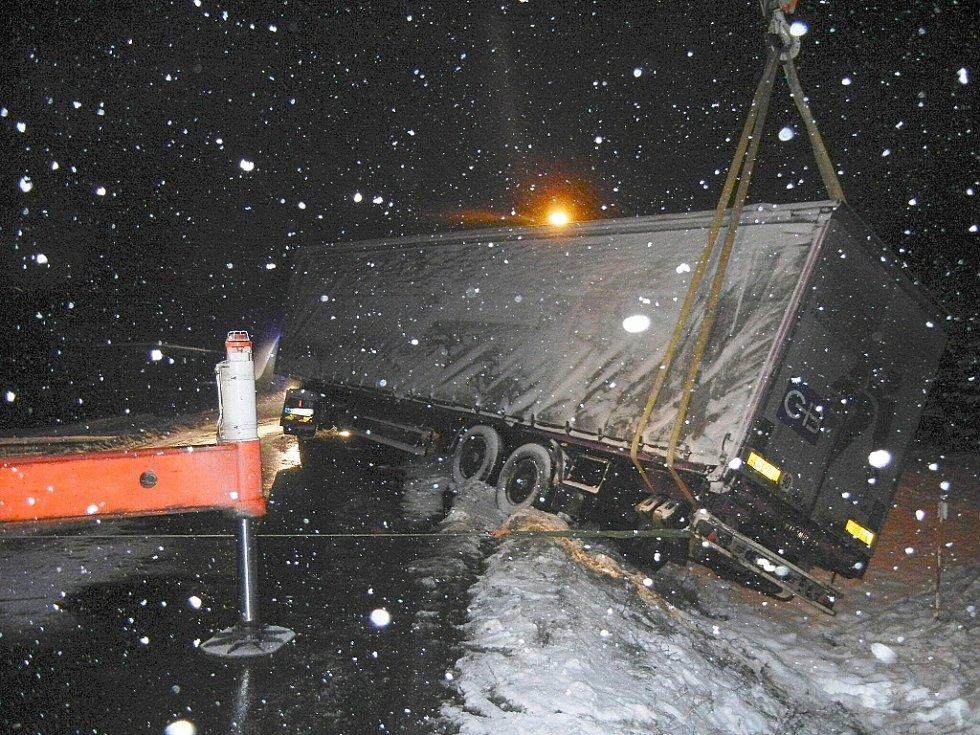Tři jednotky profesionálních hasičů zasahovaly v pátek 7. prosince brzy ráno u obce Ropice, kde v příkopu uvízla zadní část kamionu Scania.