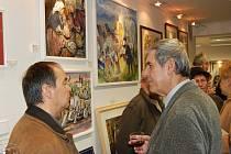 Karel Bogar (vpravo) provádí návštěvníky Galerie Pod zámkem tvorbou Elišky Servátkové.