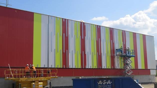 Obchodní centrum, které roste v centru Frýdku-Místku, svou barevnou fasádou mnohé obyvatele města vystrašilo. Už o prázdninách ale dostane konečnou, decentnější podobu.