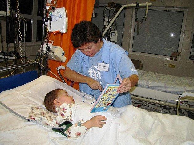 Dobrovolnice Alžběta Pavlásková (teta Bětka) s malým pacientem Františkem při prohlížení obrázkové knížky večer před spaním.
