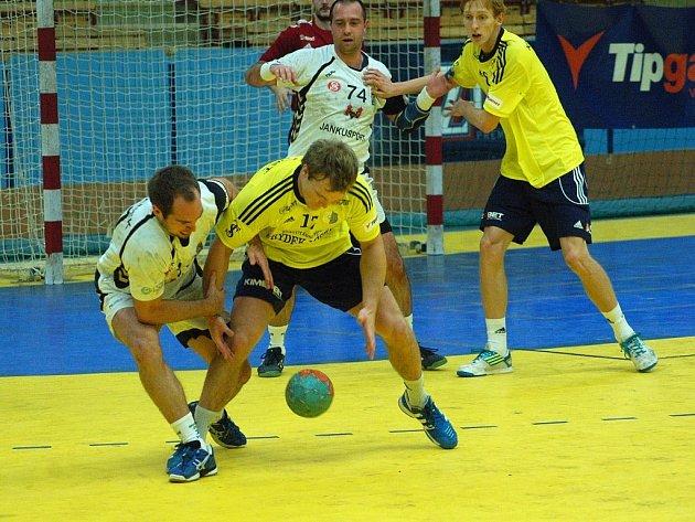 Frýdecko-místecký Tomáš Hes (ve žlutém) bojuje o míč s domácím házenkářem.
