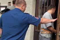 Policie odvádí zadrženého zloděje (vpravo).