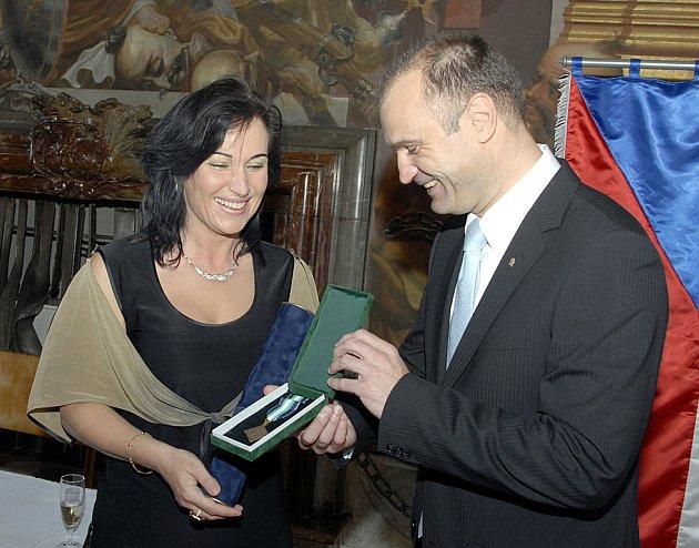 Ministr vnitra Ivan Langer předává medaili třinecké starostce Věře Palkovské.