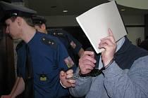 Bronislav Dimel si zakryl tvář sešitem, do něhož si během jednání zapisoval poznámky pro svou obhajobu.