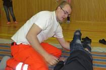 Roman Bortlíček předvádí žákům základní školy základy první pomoci.