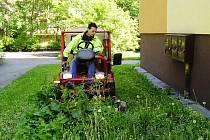 Snímek zachycuje zaměstnance technických služeb na traktorové sekačce.