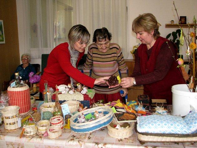 Pečovatelky centra Domovinka v Místku si spolu s jeho obyvatelkou prohlížely velikonoční výrobky, které vytvořili postižení lidé z integrovaného centra Žirafa.