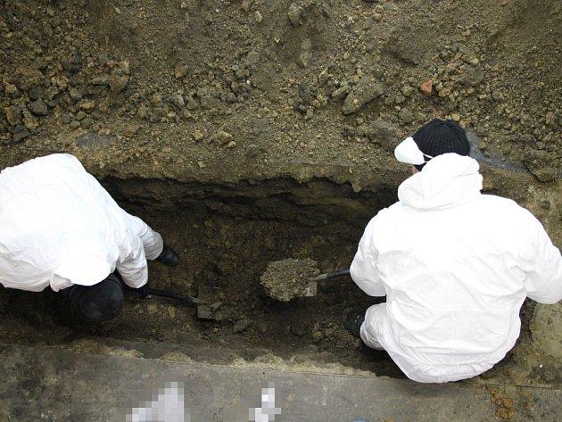 Policisté odkrývají hrob vgaráži.