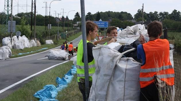 Dobrovolníci instalují bezpečnostní prvky podél závodního okruhu.